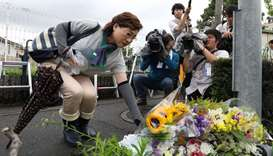 Residents place flowers for victims of a fire which hit the Kyoto Animation studio building the day