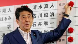 Japan's Prime Minister Shinzo Abe puts a rosette on the name of a candidate who is expected to win t
