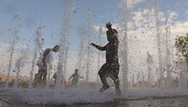 Children play in a water feature in Domino Park in Brooklyn, New York City.