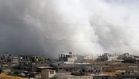 Smoke billows above buildings during a reported air strike by pro-regime forces on Khan Sheikhun in