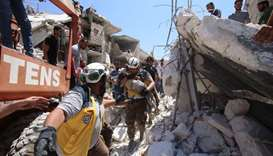 Members of the Syrian civil defence, known as the White Helmets, pull out an injured but alive child