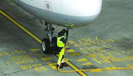 A ground crew member connects a fuel hose to an Airbus A321 aircraft, operated by Deutsche Lufthansa