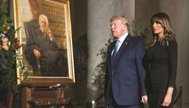 President Donald Trump and First Lady Melania Trump walk past a painting of the late Supreme Court J