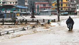 A resident walks through floodwaters after the Balkhu River overflowed following monsoon rains at th