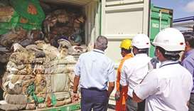 Customs officials inspect the load of a container at a port in Colombo yesterday.
