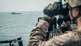 A US Marine observes an Iranian fast attack craft from USS John P. Murtha during a Strait of Hormuz