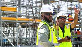 Workers at Al Rayyan Stadium oversee the construction progress