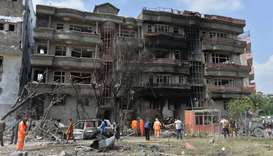 Afghan security forces and municipality workers gather at the site of an attack in Kabul