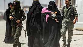 An internal security patrol escorts women, reportedly wives of Islamic State (IS) group fighters, in