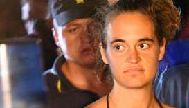 Carola Rackete is escorted off the ship by police and taken away for questioning, in Lampedusa