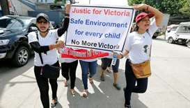 Protesters hold signs during a march demanding justice for a child rape case, in Yangon, Myanmar