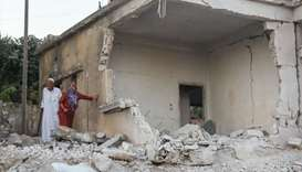 Syrians inspect the damage following reported regime airstrikes on the town of Muhambal, in the nort