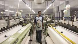 A worker inspects fabric on looms at a textile manufacturer in Karachi. Statistics in the World Bank