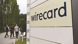 Visitors pass a sign at the entrance to the Wirecard headquarters in Munich. Once a darling of the f