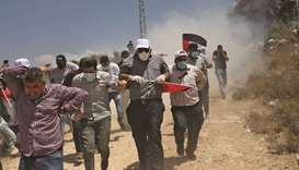 Palestinian protesters flee clashes with security forces during a protest against Jewish settlements