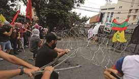 Protesters pull barbed-wire closing off a street during an anti-US demonstration near the United Sta