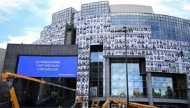 Workers paste portraits of healthcare workers on the facade of the Opera Bastille, at the initiative