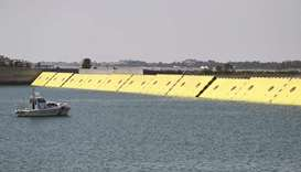 Yellow mobile barriers are seen above the surface of the water during tests of flood barrier project