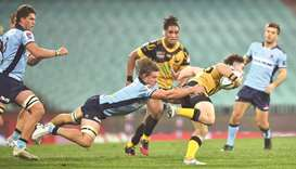 Waratahs player Michael Hooper tackles Western Force player Jack McGregor during their Super Rugby m