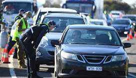 A Victoria Police officer works at a vehicle checkpoint created in response to an outbreak of COVID-