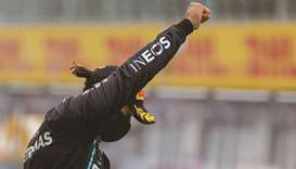 Mercedes' British driver Lewis Hamilton raises a fist on the podium after winning the Styrian Grand