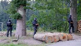 Police officers stand outside a wooded area on a road near Oppenau, southwestern Germany