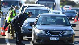 Victoria Police and ADF personnel work at a vehicle checkpoint along the Princes Freeway outside of