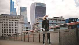 A woman wearing a face mask, walks across London Bridge away from the City of London. Britain's econ