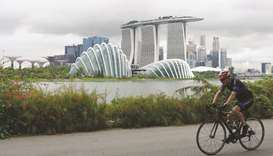 A cyclist rides along Marina Bay overlooking the financial business district in Singapore. The city-