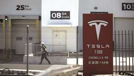 A worker walks past gates at the Tesla Inc Gigafactory in Shanghai. Tesla needs to succeed in China