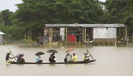 People ride on a boat through flooded waters in Sunamgong.