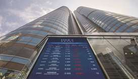 A screen displays stock figures outside the Hong Kong Stock Exchange. The Hang Seng closed down 1.1%