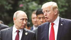 FILE PHOTO: US President Donald Trump and Russia's President Vladimir Putin talk during the family p