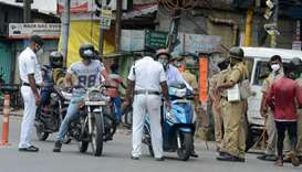 Police personnel stop motorists on a street after a new lockdown was imposed as a preventive measure