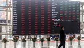 A man wearing a protective mask walks past an electronic stock board at the Shanghai Stock Exchange.