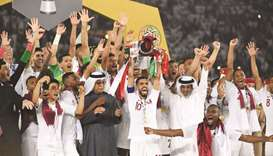 In this February 1, 2019, picture, Qatar's players celebrate with the trophy in the presence of QFA