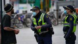 Police officers in protective face masks patrol a street in Melbourne after it became the first city