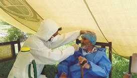 A paramedic wearing protective gear takes a nasal swab of 103-year-old Abdul Alim, to be tested for