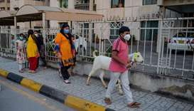 Children wearing face masks walk with a goat ahead of Eid al-Adha in Rawalpindi