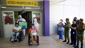 Patients who recovered from the coronavirus disease sit in wheelchairs after being released from the