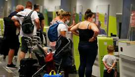 British tourists returning to UK, check in their luggage, as Britain imposed a two-week quarantine o
