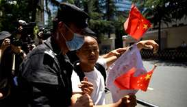 "A man holds a banner and shouts ""Chinese government is great"" is escourted by policemen in front of"