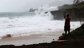 A beach goer watches the big waves wash up on Pounder's Beach in Laie, Hawaii as Hurricane Douglas m