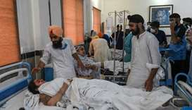Sikh people gather around injured victims treated at a hospital following the accident between a tra