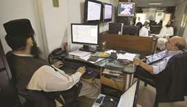 Traders work at the Pakistan Stock Exchange. The PSX announced that it will set up a fund to financi