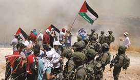 Palestinian demonstrators gather in front of Israeli forces during a protest against the plan to ann