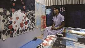 German-Ghanaian artist Zohra Opoku sits in front of her project at the studio in Kehinde Wiley's art