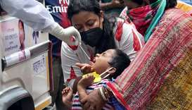 A girl reacts as a healthcare worker, sitting inside an ambulance, takes a swab from her to test for