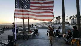 An American flag flies as people gather at Venice Skate Park, which remains open along the closed an