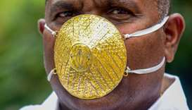 Indian man wears gold face mask to ward off coronavirus